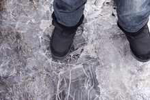 Child Steps On Frozen Puddle With Thin Ice