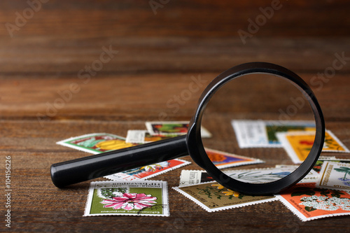 Canvastavla a small pile of expensive and collectible stamps with a magnifying glass on wood