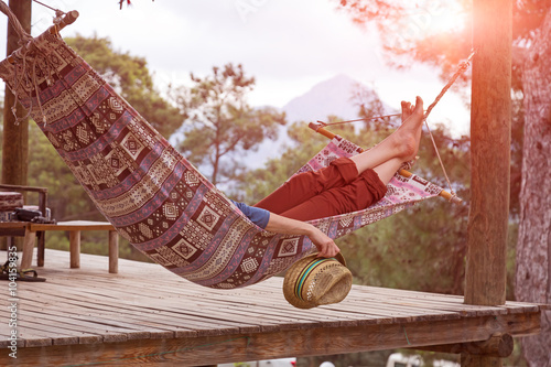 Person relaxing lying in Hammock at rural cottage garden