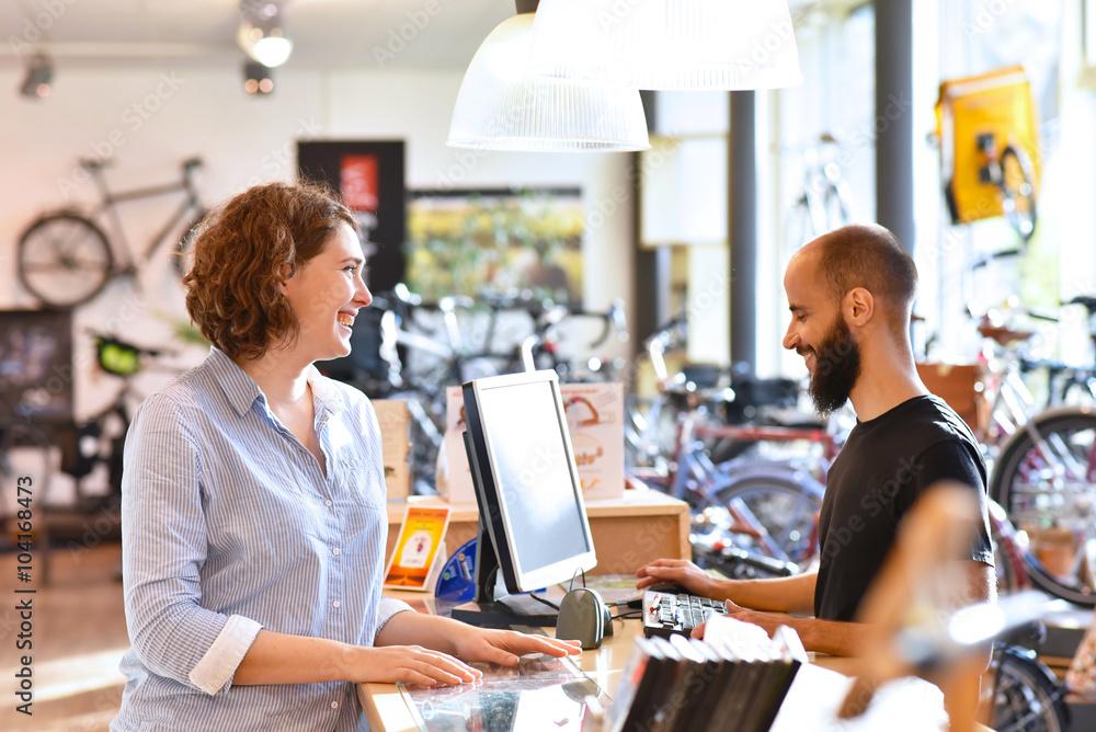 Fototapeta Lifestyle Shopping - junge Frau kauft in einem Fahrradladen ein, Beratung durch Verkäufer