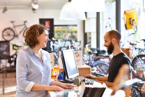 Canvas Lifestyle Shopping - junge Frau kauft in einem Fahrradladen ein, Beratung durch