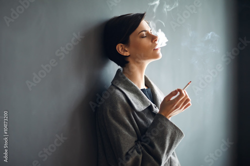 Fotografía Portrait of fashionable woman smoking a cigarette on dark backgr