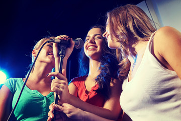 Fototapeta happy young women singing karaoke in night club