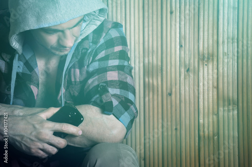 Fotografering  Hipster young man in the hood, sitting, holds phone and look down on wooden brown background with copy space right