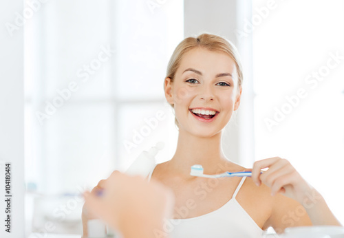 Photo woman with toothbrush cleaning teeth at bathroom