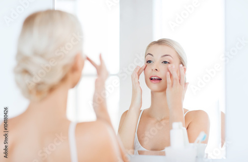 Fotografie, Obraz  happy woman applying cream to face at bathroom