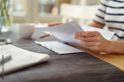 Fotografía  Frau am sentado Küchentisch und einen liest breve