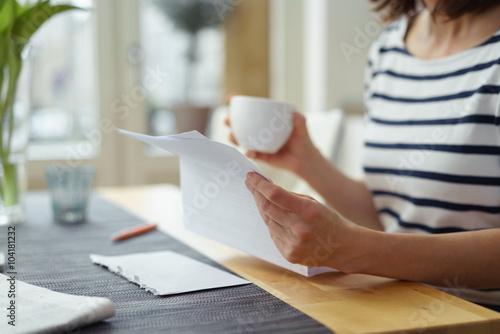 Fotografia  frau sitzt am küchentisch und liest einen brief