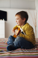 Child Playing Guitar In The Room