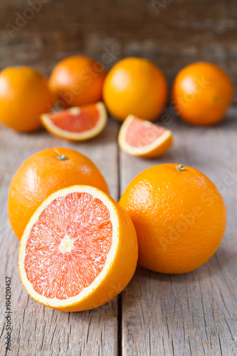 Canvas Prints Fruits Fresh oranges with slices on wooden background.