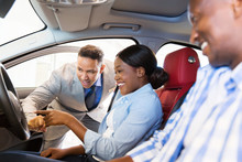 Salesman Showing New Car To African Couple