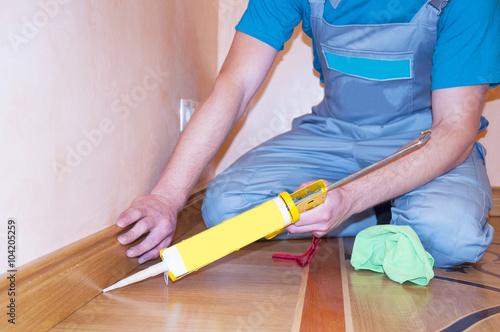 Repairman Installing Skirting Board Oak Wooden Floor With Caulking