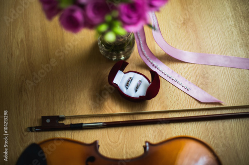 Fotografía  Wedding rings in the red box, a violin and bow, wedding flowers, wedding bouquet