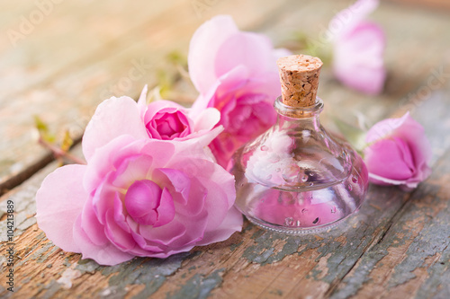 Foto  Bottle of oil and pink rose flowers