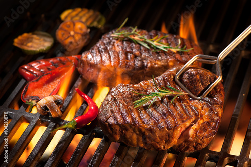 Beef steaks on the grill - 104218878