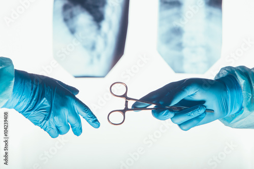 Two surgeons working and passing surgical equipment in the operating room Plakat