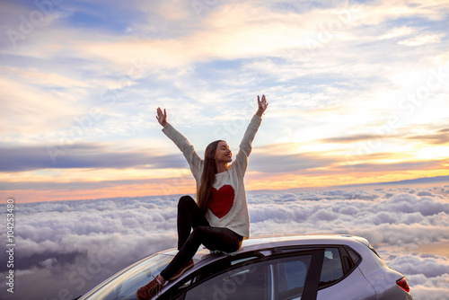 Canvas Print Young woman in sweater with heart shape rising hands sitting on the car roof above the clouds on the sunrise