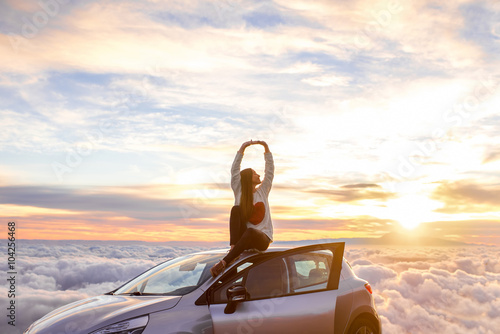 Tablou Canvas Young woman in sweater with heart shape rising hands sitting on the car roof above the clouds on the sunrise