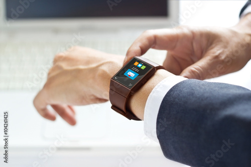Fotografia  Businessman using smartwatch on laptop background