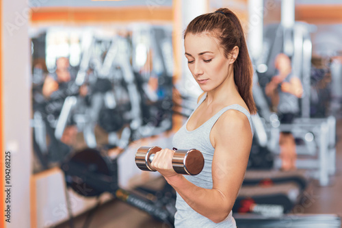 Spoed Foto op Canvas Fitness Strong woman weightlifting at the gym looking happy and working on her biceps