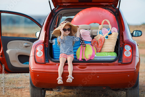 Fotografie, Obraz Little girl in straw hat sitting in the trunk of a car