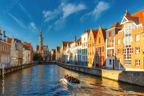 Foto op Aluminium Brugge Tourist boat on canal Spiegelrei and Jan Van Eyck Square in the morning in Bruges, Belgium