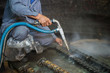 canvas print picture - Worker is cleaning the machine equipment by using the air pressure sand / dryice blasting