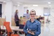 portrait of young business woman at office with team in backgrou