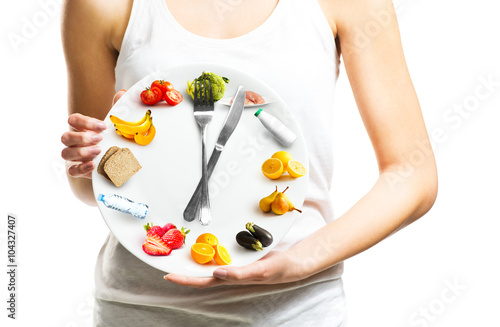 Fototapeta Beautiful young woman holding a plate with food, diet and time concept close up  obraz