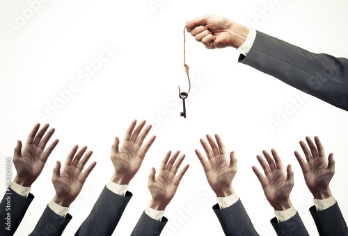 Vászonkép hand of a businessman holding a fish hook with a key over many hands of business