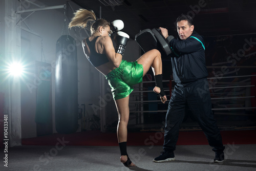 Tablou Canvas Boxing girl doing knee kick