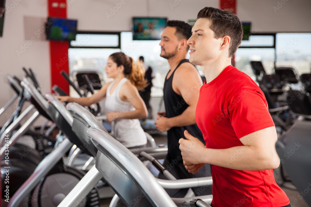 Fotografie, Obraz Men and women jogging on a treadmill