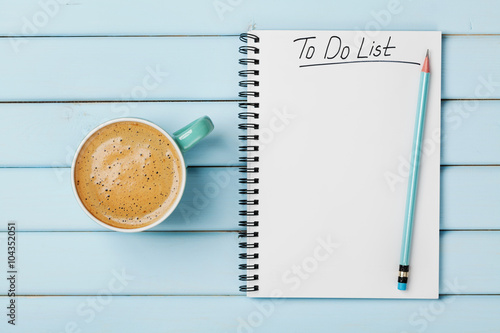 Photo  Coffee cup and notebook with to do list on blue rustic desk from above, planning