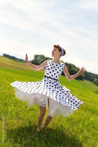 Fotografie, Obraz Pin-up girl tanzt auf einer Wiese Rock & Roll
