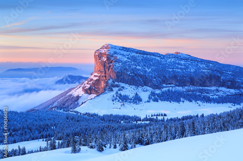 Leinwand Poster Winter forest on mountain range in French Alps during a colorful sunset