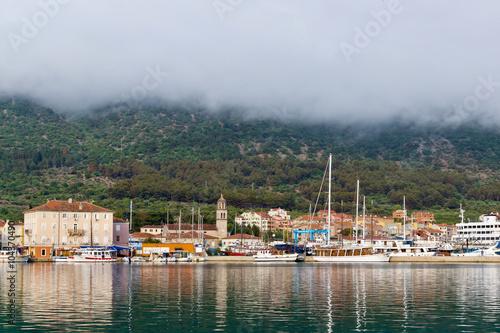 In de dag Stad aan het water Порт города Крес под густыми облаками, Хорватия