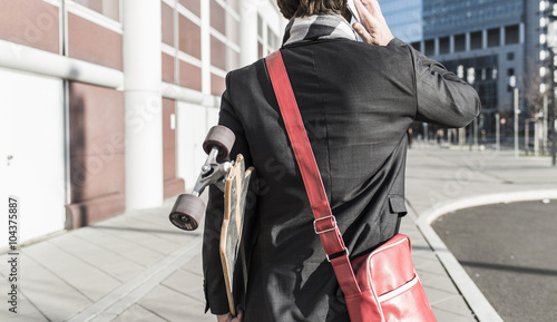 Germany, Frankfurt, Young businessman walking the city with skateboard, using mobile phone