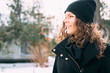 Happy smiling girl with curly hair in a coat and hat in winter p