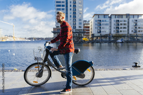 Ireland, Dublin, young man at city dock with city bike Poster