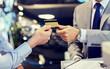 customer giving credit card to car dealer in salon