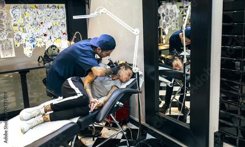 Woman receiving tattoo in tattoo studio