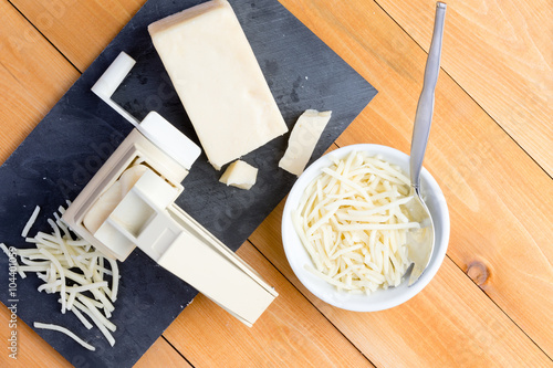 Preparing grated gruyere cheese for cooking