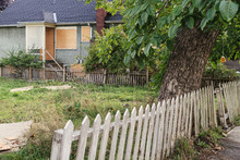 Vacant Unkept Yard With Rickety Fence And Boarded Up House