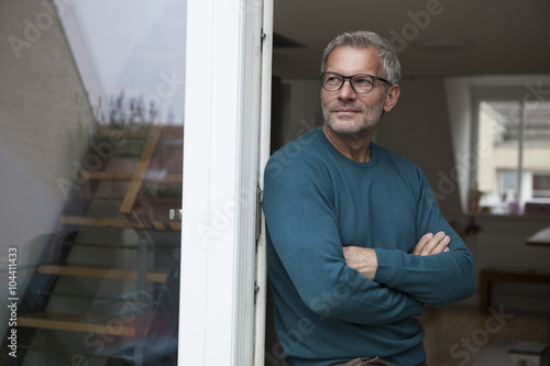 Mature man leaning against balcony door