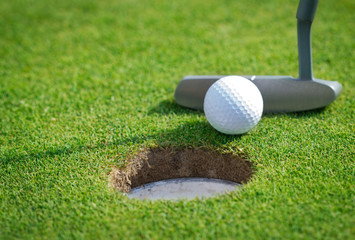 Fototapeta Golf Close-up of golf hole with putter and ball