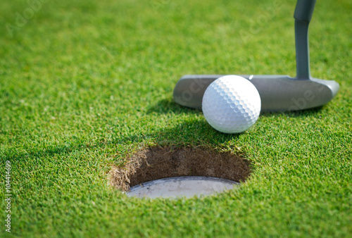 Close-up of golf hole with putter and ball - 104414699