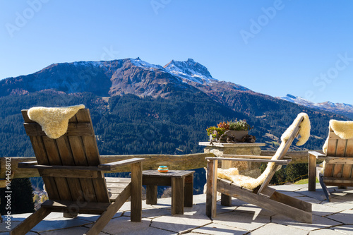 Wooden easy chairs at a mountain lodge terrace, Klosters Switzer Canvas Print