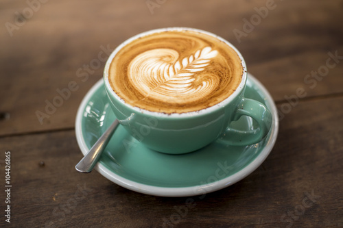 Leinwand Poster hot cappuccino with latte art on wood background