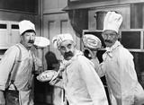 Trzech kucharzy trzyma ciasta do walki w kuchni - 104427604