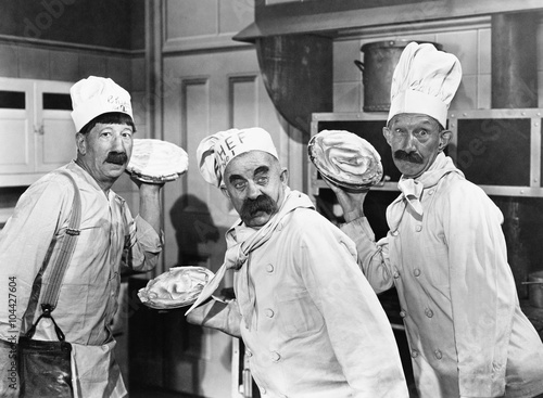 Fotografie, Obraz  Three chefs holding pies for a fight in the kitchen